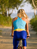 Female cyclist rear view. Female cyclist on bicycle outdoors summer rear view Stock Image