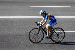 Female cyclist rides a racing bike on road stock photography