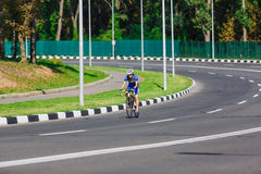 Female cyclist rides a racing bike on road Stock Photo