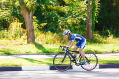 Female cyclist rides a racing bike on road Royalty Free Stock Images
