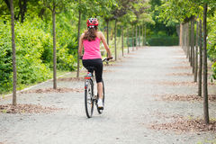 Female Cyclist Riding Away On Bicycle stock photo