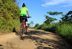 cyclist riding mountain bike on country road Royalty Free Stock Photos