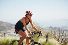 Female cyclist riding racing bicycle Royalty Free Stock Photos