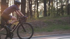 Female cyclist riding road bicycle in the park with the sun shining through trees. Cinematic cycling concept. Slow motion.  stock video footage