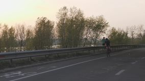 Female cyclist riding towards camera at sunset. Cinematic cycling concept. Female cyclist riding towards camera at sunset. Cinematic cycling concept stock video