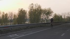 Female cyclist riding towards camera at sunset. Cinematic cycling concept. Slow motion.  stock video footage
