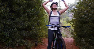 Female cyclist standing with mountain bike. Excited female cyclist standing with mountain bike in forest, 4k stock footage