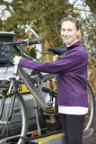 Female Cyclist Taking Mountain Bike From Rack On Car Royalty Free Stock Photos