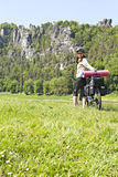 Female cyclist traveling on a bicycle with a load. Stock Image