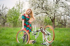 Female cyclist with vintage white bicycle in spring garden stock photos