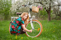 Female cyclist with vintage white bicycle in spring garden Royalty Free Stock Images