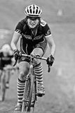 A female cycloross racer climbs muddy hill Royalty Free Stock Photography