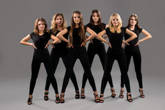 Female dance group pose in artistic black costumes Royalty Free Stock Image