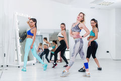 Female dance team wearing sports bra and leggings posing in studio standing backside and sideways turning to camera Royalty Free Stock Photos