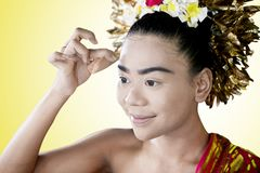 Female dancer applying powder puff on her face. Female traditional dancer applying powder puff on her face before performing in the studio with yellow background stock images