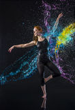 Female Dancer Being Splashed with Colorful Water Stock Photography