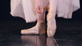 A close-up view on ballerina shoes tied up. A female dancer crisscrosses ribbons on her ballet shoes stock video