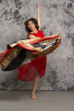 Female dancer with fabric, wearing a red dress, grey background. Royalty Free Stock Photo