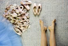 Female dancer feet near a group of used pointe shoes Stock Image