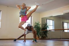 Female dancer with friend jumping in studio Royalty Free Stock Photography