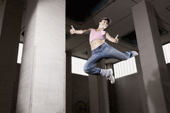 Female dancer jumping with thumbs up. Smiling sexy dancer girl jumping high with both thumbs up in old grungy factory hall, copy-space on empty pillar Royalty Free Stock Photo