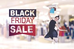 Female dancer jumps with Black Friday Sale text. Female dancer holding shopping bags while jumping with Black Friday Sale text royalty free stock photography