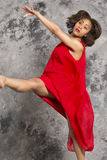 Female dancer kicking, wearing a red dress, grey background. Stock Images