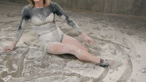 The female dancer performs a dance piece on the floor in white dust. The dancer girl performs art dance in a black body. T-shirt, shorts and ballet shoes on the stock video footage