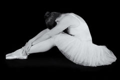 Female dancer sit on floor looking sad in artistic conversion. Black and white Stock Photography
