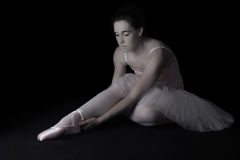 Female dancer sit on floor looking sad in pink tutu low key Royalty Free Stock Photo