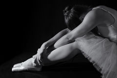 Female dancer sit on floor looking sad in pink tutu low key Royalty Free Stock Photo