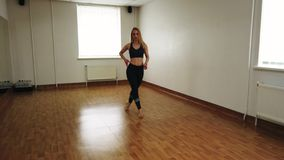 Female dancer training dance while rehearsing in dance studio. Elegant attractive female dancer improvising contemporary style dance while rehearsing in dance royalty free stock images