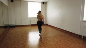 Female dancer training dance while rehearsing in dance studio. Elegant attractive female dancer improvising contemporary style dance while rehearsing in dance royalty free stock photos