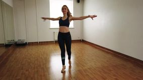 Female dancer training dance while rehearsing in dance studio. Elegant attractive female dancer improvising contemporary style dance while rehearsing in dance