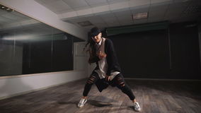 Female dancer in white shirt, black trousers and black cap showing jazz modern dancing. Girl is expressively dancing and