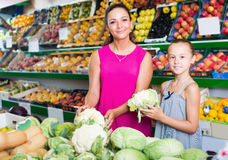 Female with daughter buying cabbage in vegetables. Happy female with daughter buying cabbage in vegetables section in supermarket Stock Photography