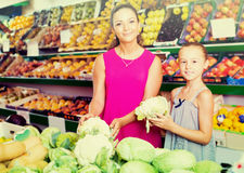 Female with daughter buying cabbage in vegetables. Happy female with daughter buying cabbage in vegetables section in supermarket stock images