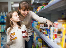 Female with daughter choosing canned goods in food store Royalty Free Stock Photos