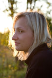 Female on a decline. Portrait of the young blonde  girl shined with the sunset sun Stock Image