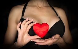 Female decolletage, black dress. Woman holds a red silk heart in her hands, low key. stock image