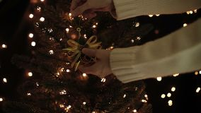 Female decorate Christmas tree with gold star decoration on bokeh lights background.  stock video