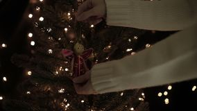 Female decorating the fairy garland on a Christmas tree with bokeh lights background.  stock video