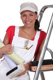 Female decorator. Holding rolls of wallpaper Royalty Free Stock Image