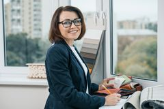 Female decorator interior designer at workplace with fabric samples. Smiling female in jacket, glasses looking at the camera royalty free stock photo
