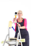 Female decorator on a ladder. Female decorator wearing dungarees on a ladder doing house redecoration with a roll of wallpaper and brushes isolated on white Royalty Free Stock Photography