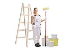 Female decorator with paint roller standing in front of ladder Stock Images
