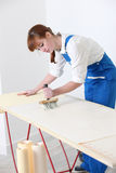 Female decorator pasting wallpaper Royalty Free Stock Photo