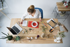 Female decorator with wreath, dry flowers and laptop at workplace. Overhead view of female decorator with wreath, dry flowers and laptop at workplace Royalty Free Stock Images