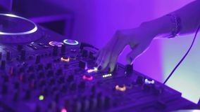 Female deejay performing at nightclub party, mixing music records for public