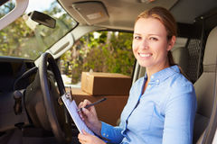 Female Delivery Driver Sitting In Van Filling Out Paperwork Stock Photography